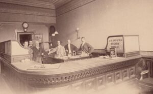 Undated photograph of E.W. Churchill (second from left) behind the desk at the Goodman Bank.